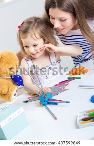 a young mother and her little daughter paint together and made from plasticine and pencils hedgehog. mother and child playing with Teddy bear - stock photo