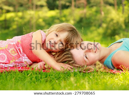 a young mother and her little daughter playing on grass - stock photo