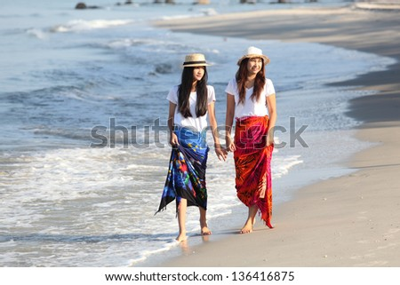 A young mother having fun with her daughter on the beach - stock photo