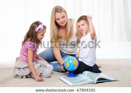 A young mother, her daughter and young son studying geography. Atlas and the globe.