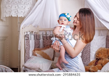 A young mother holding a baby daughter in her arms the children's room. The concept of a happy family. - stock photo