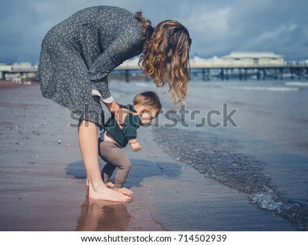 A young mother is helping her little baby walk on the beach