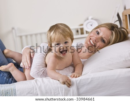 A young mother is holding her baby daughter on the bed.  They are smiling and looking away from the camera.  Square framed shot. - stock photo