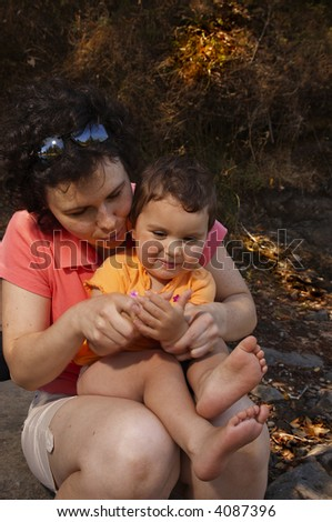 A young mother is playing with her toddler daughter on a forest lake shore.