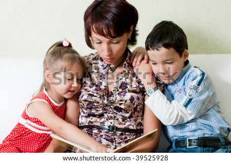 a young mother is reading a book to her kids, a boy and a girl, sitting on a sofa - stock photo