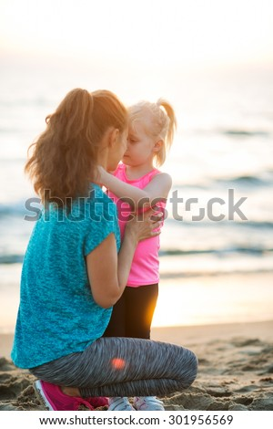 A young mother kneels down on the beach next to her daughter to share a little Eskimo kiss. Both are wearing workout gear, and the sun is setting. - stock photo