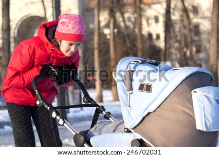 A young mother looks at the baby in a stroller for a walk in the park - stock photo