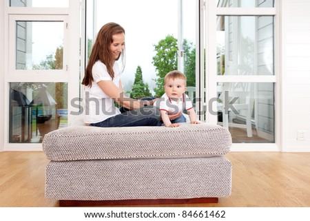 A young mother playing with happy son in beautiful living room interior
