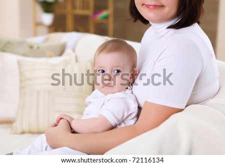 a young mother playing with her infant baby at home