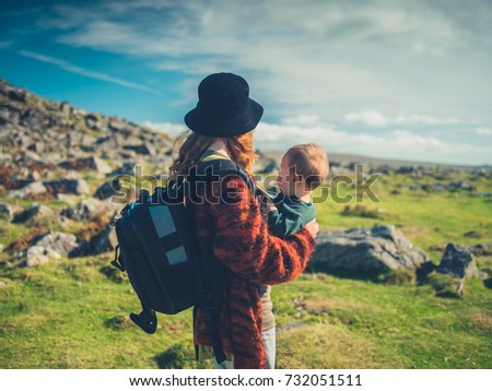 A young mother with a baby and a big backpack is trekking through the wilderness