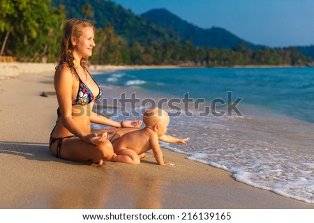 A young mother with a child having fun on a tropical beach.. Nature. Outdoor portrait of a happy family. Joy.