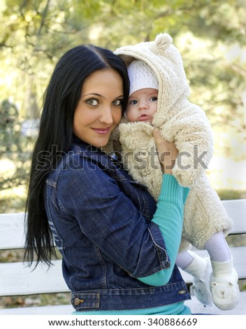 a young mother with a little child at her arms, outdoors - stock photo