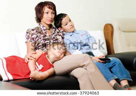 a young mother with two kids, a boy and a girl, is sitting on a sofa and watching a tv