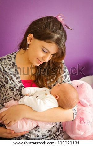 A young mothers special bonding moment with her newborn baby - stock photo