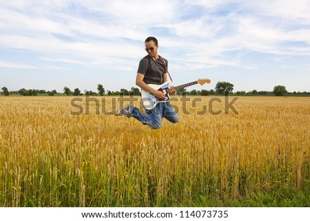 A young musician with his electric guitar jumping outside in a wheat field. - stock photo