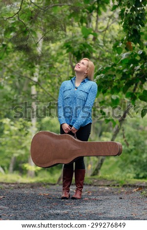A young musician woman in an outdoor setting with a guitar case and guitar.