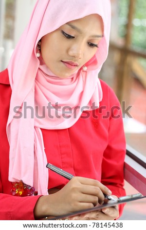A young  muslim businesswoman writing a report file - stock photo