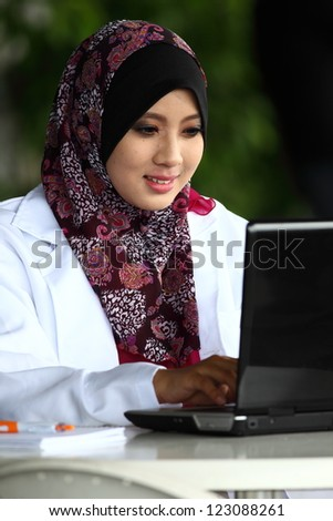 A young muslim girl doctor with hijab (head scarf) typing something on the laptop