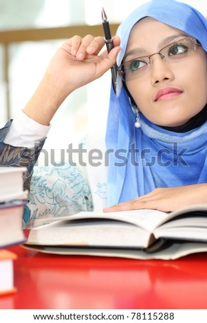A young muslim girl reading a book while thinking - stock photo