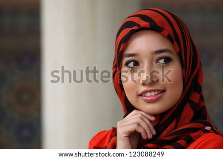 A young muslim girl with hijab (head scarf) looking to something that interest her (with copyspace) - stock photo