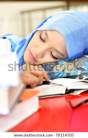 A  young muslim woman sleeping while reading a book - stock photo