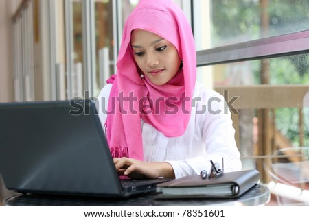 A young muslim woman using laptop - stock photo