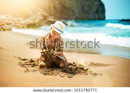 A young naturalist found a turtle on a sandy beach. The boy sits on his knees in the sand and examines the turtle. Sea surf on the background