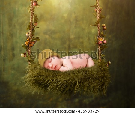 A young newborn baby is sleeping on a flower swing in an enchanted forest for a dream fairy concept. - stock photo