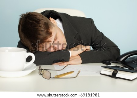 A young office worker was tired and fell asleep at the table - stock photo