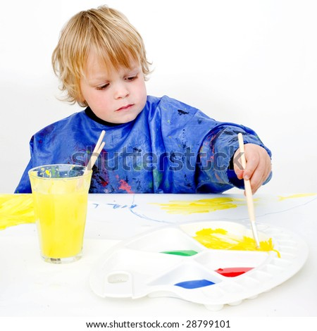 A young painter reaching for the yellow poster paint on his palette