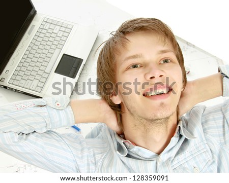 A young pensive man at his workplace, from above - stock photo