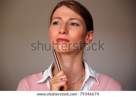 A young pensive woman looking up and holding a pen in her hand - stock photo