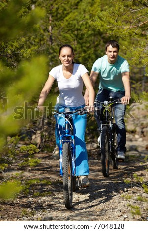 A young people riding bicycles in wood - stock photo