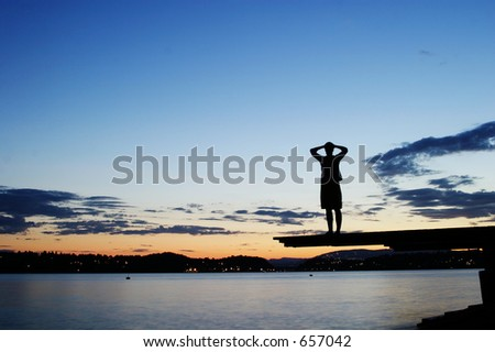 A young person sitting on a dock at dusk, at the fjord in Oslo, Norway - stock photo