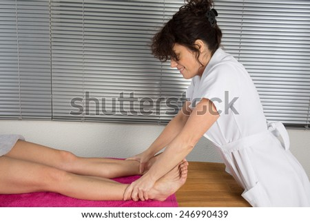 A young physical therapist giving a leg massage in a health center - stock photo