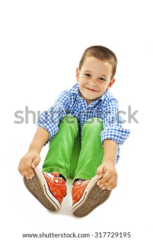 A young playful boy sitting on the floor. Isolated on white background