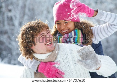 A young playful couple has a fun winter time in a snow park