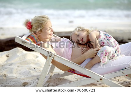 a young pregnant mother sits in the deck chair with her daughter on the beach