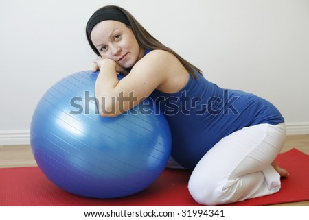 A young pregnant woman doing a relaxation exercise using a fitness ball on an exercise mat. - stock photo