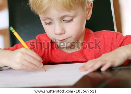 a young, preschool aged child is working on a drawing on a white piece of paper with a writing pencil - stock photo