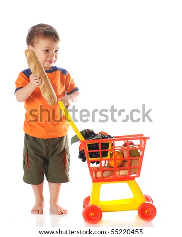 A young preschooler choosing a loaf of bread to put into his colorful shopping cart.  Isolated on white. - stock photo