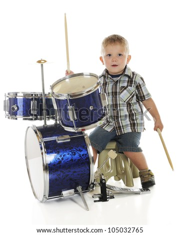 A young preschooler looking at the viewer as he plays on a drum set.  On a white background. - stock photo