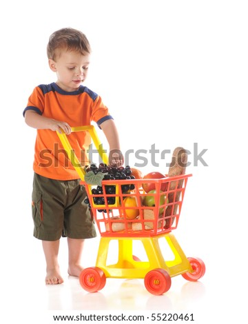 A young preschooler with a load of groceries in his plastic shopping cart.  isolated on white.