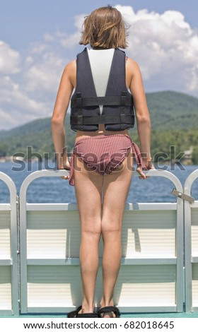 A young preteen girl standing on the front of a pontoon boat with life jacket on.