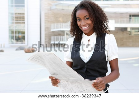 A young pretty african american business woman at office reading newspaper - stock photo