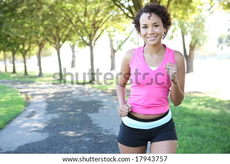 A young pretty african american woman jogging in the park - stock photo