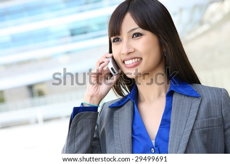 A young, pretty asian business woman at office building on cell phone