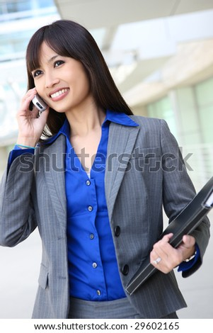 A young, pretty asian business woman at office building on cell phone - stock photo