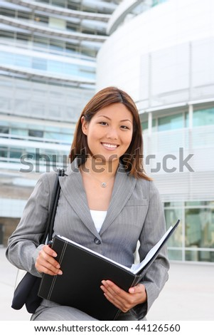 A young, pretty asian business woman at office building with notebook - stock photo