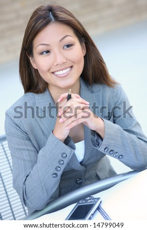 A young, pretty asian business woman at work - stock photo